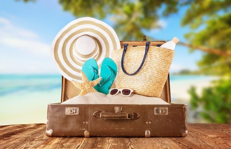 Rétro bagage avec des accessoires de vacances de plage d'été placés sur l'OE images stock