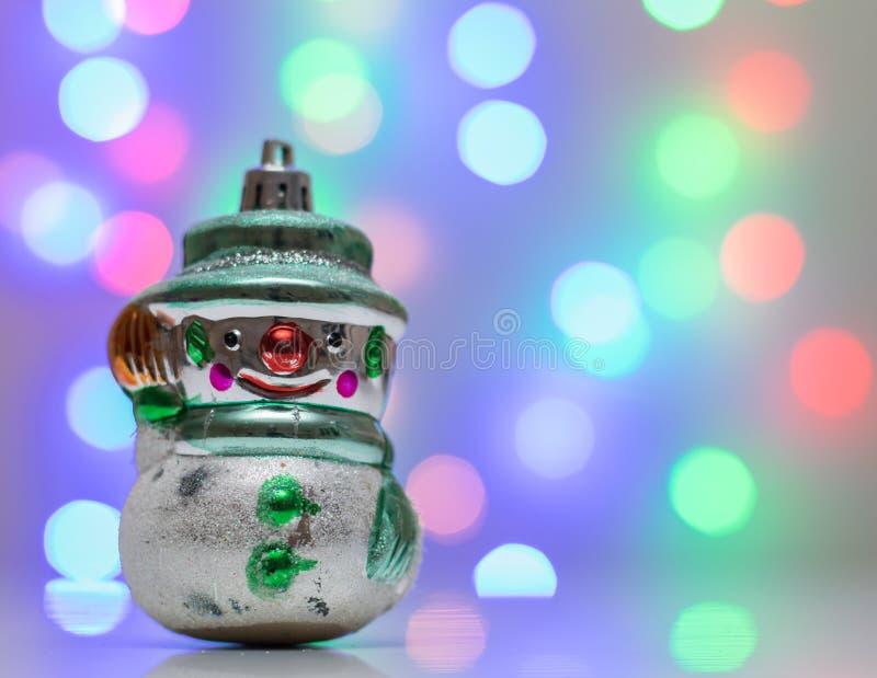 Rétro bonhomme de neige de jouet de Noël dans le bokeh de fond photographie stock