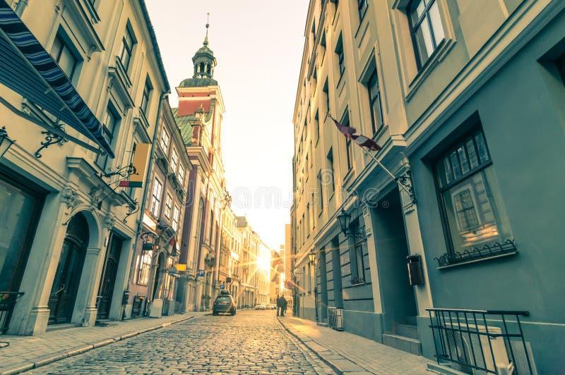 Rétro carte postale de voyage de vintage de rue médiévale étroite à Riga photos stock