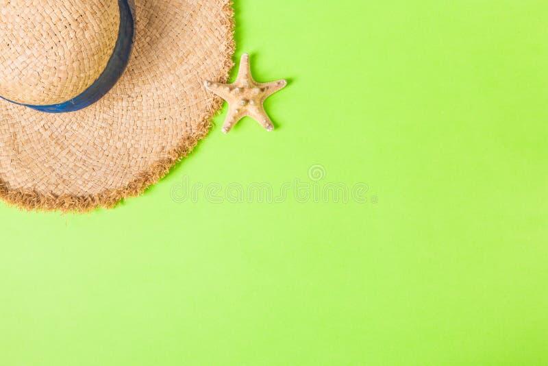 Rétro chapeau de paille jaune avec la vue supérieure seastar avec l'espace de copie concept d'été sur le fond vert photos stock