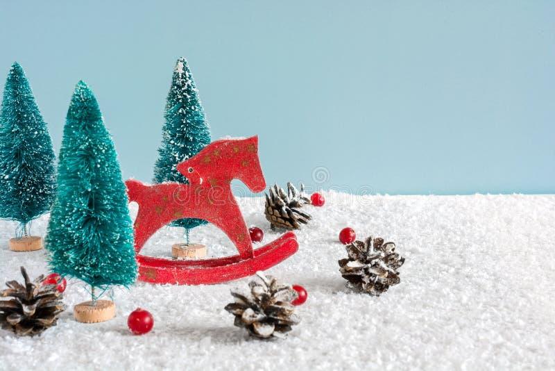 Rétro cheval de jouet de Noël avec des sapins, des baies rouges et des cônes de pin sur la table en bois couverte de neige photo stock