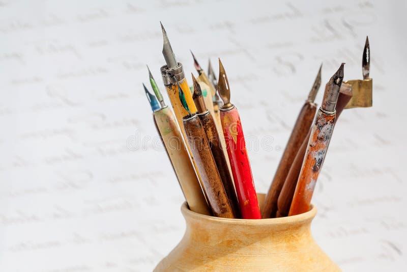 Rétro collection de stylo-plume de style dans la cruche en céramique, fond abstrait de lettres macro vue, profondeur de champ photo stock