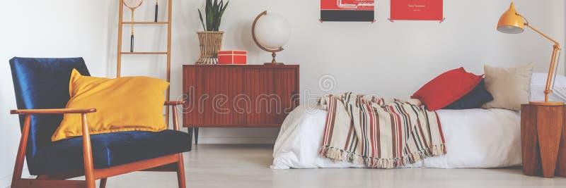 Rétro fauteuil de velours en vraie photo de l'intérieur blanc de chambre à coucher avec le décor de cru photo libre de droits