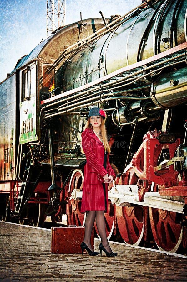 Rétro femme avec la valise à la station de train. photo stock
