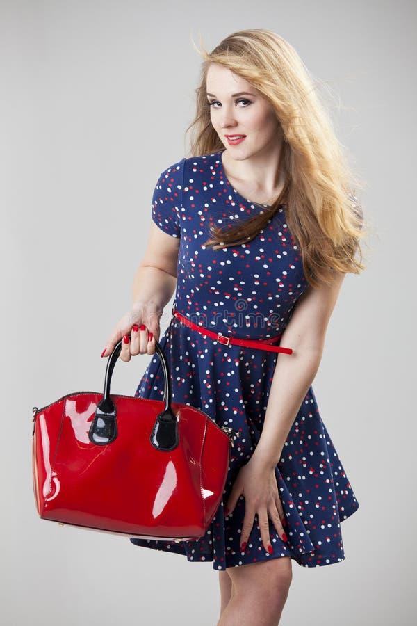 Rétro femme avec le sac rouge image stock
