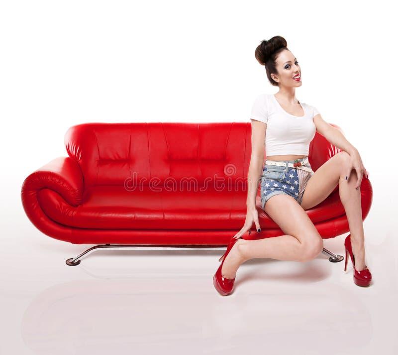 Rétro fille Pin-vers le haut sur le divan en cuir rouge images libres de droits