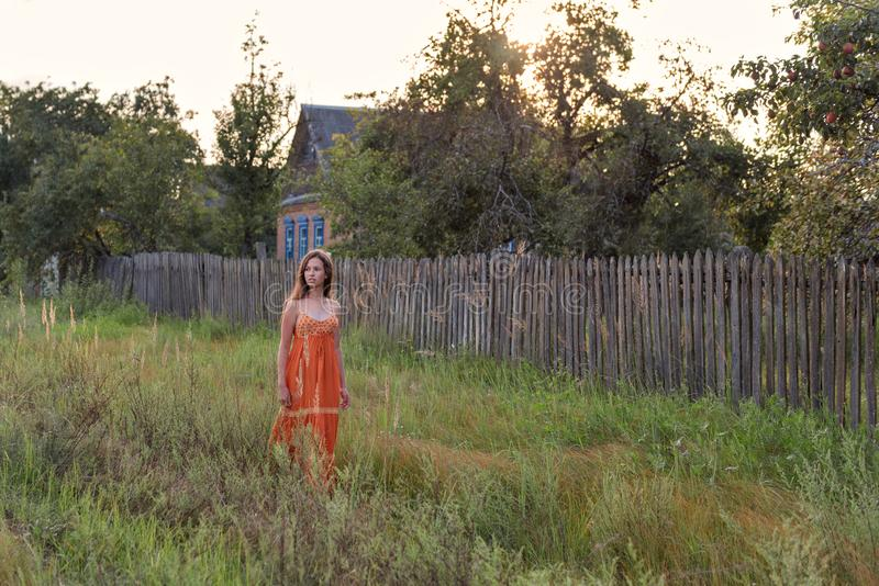 Rétro fille seule effrayée dans la campagne marchant le long de la haute herbe le soir le long des bâtiments abandonnés du villag photos stock