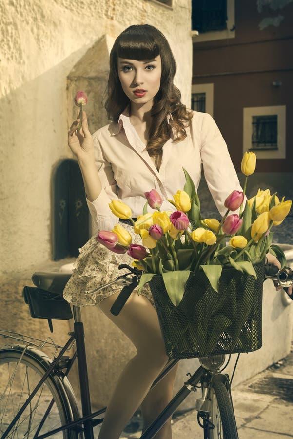 Rétro goupille- sexy sur le vélo dans la vieille ville avec des tulipes images libres de droits