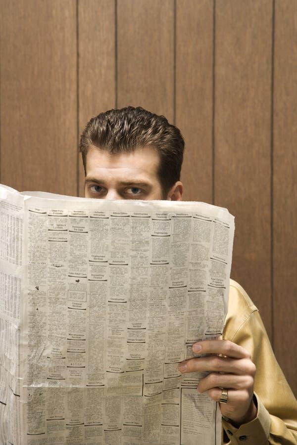 Rétro homme d'affaires jetant un coup d'oeil au-dessus du journal. images libres de droits