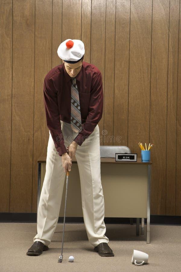 Rétro homme d'affaires jouant au golf dans le bureau. photographie stock