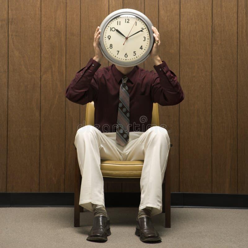 Rétro horloge de fixation d'homme d'affaires au-dessus de visage. photo stock