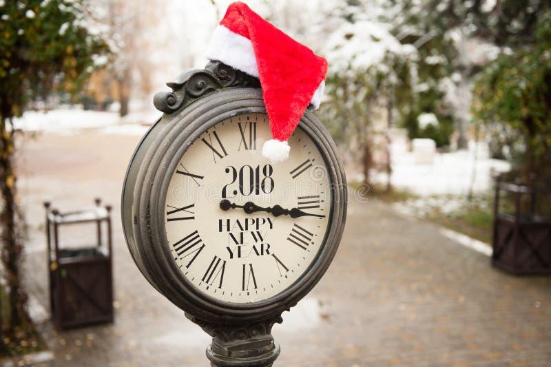 Rétro horloge de rue avec le chapeau de la bonne année 2018 et de la Santa Claus d'inscription sur eux photographie stock
