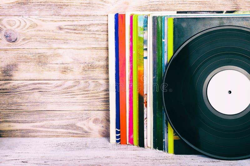 Rétro image dénommée d'une collection du vieux disque vinyle lp avec des douilles sur un fond en bois avec l'espace de copie modi image stock