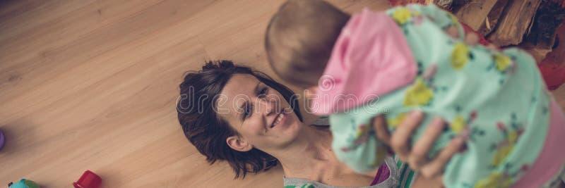 Rétro image de vue large de la jeune mère heureuse jouant avec son bab images stock