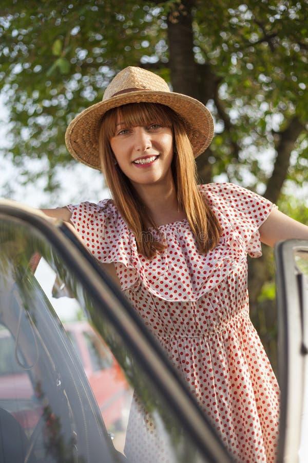 Rétro jeune femme de style se tenant à côté de la voiture images libres de droits