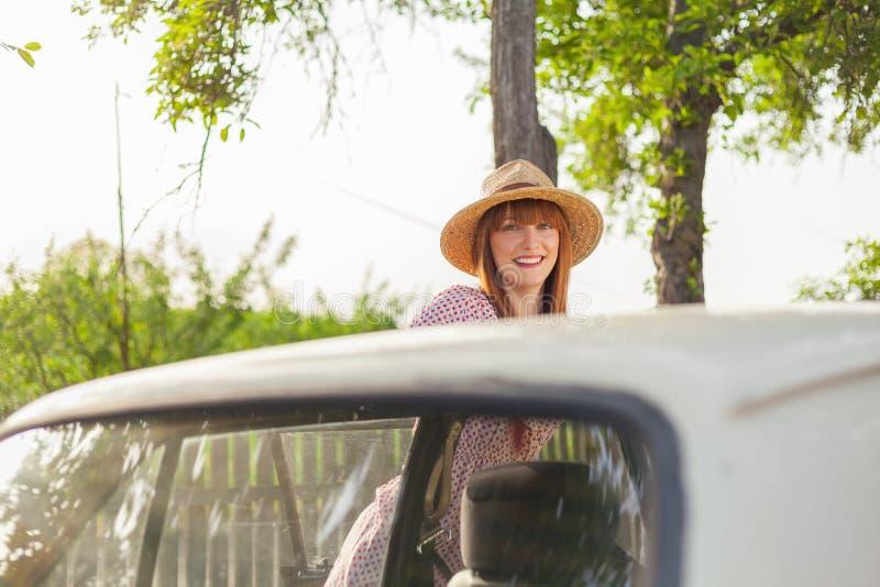 Rétro jeune femme de style se tenant à côté de la voiture photos libres de droits