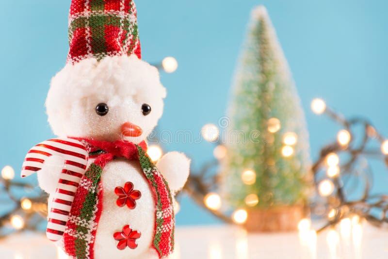 Rétro jouet de bonhomme de neige avec l'écharpe et les lumières de Noël rouges et arbre à l'arrière-plan brouillé photos stock