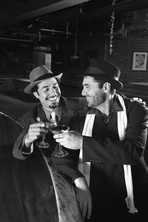 Rétro mâles s'asseyant au bar. photo stock