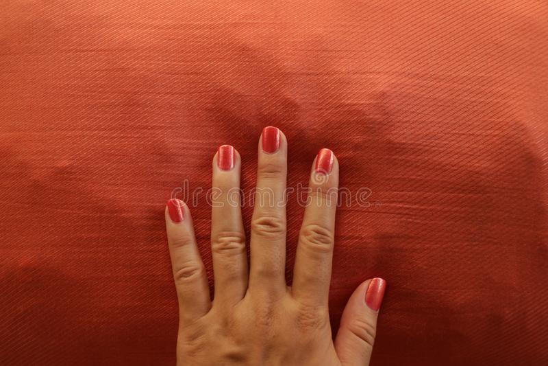 Rétro orange peinte à la main Manicured sur le fond assorti photographie stock