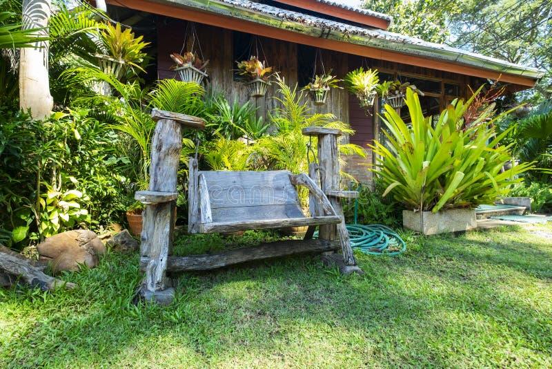 Rétro oscillation en bois dans l'arrière-cour verte de jardin Détendez et paisible dans la pelouse de nature images stock