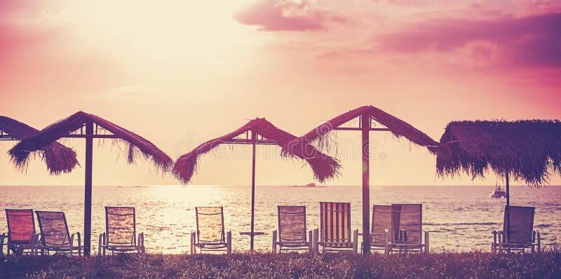 Rétro photo filtrée des chaises et des parapluies de plage au coucher du soleil photographie stock