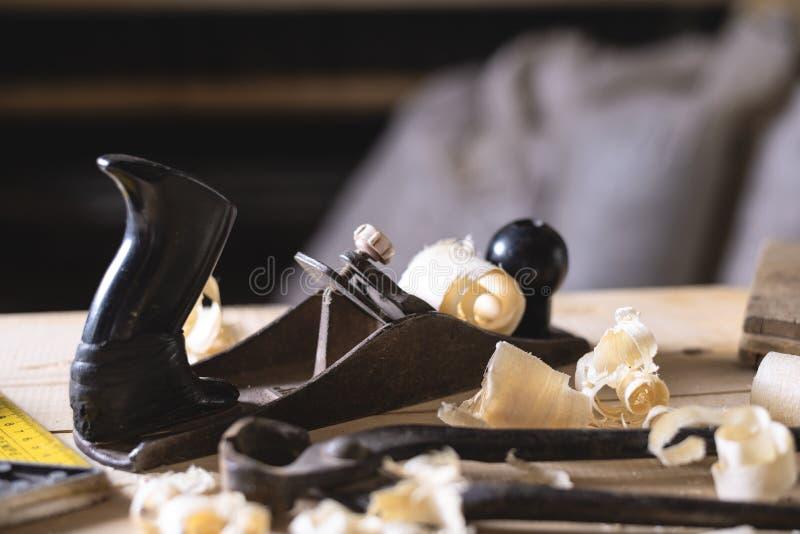 Rétro planeuse de main avec des copeaux, coin, coupant des pinces, sur la table en bois avec des planches image libre de droits