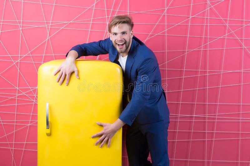 Rétro réfrigérateur de prise heureuse d'homme Sourire macho avec le réfrigérateur homme d'affaires dans le procès formel Meubles  photographie stock libre de droits