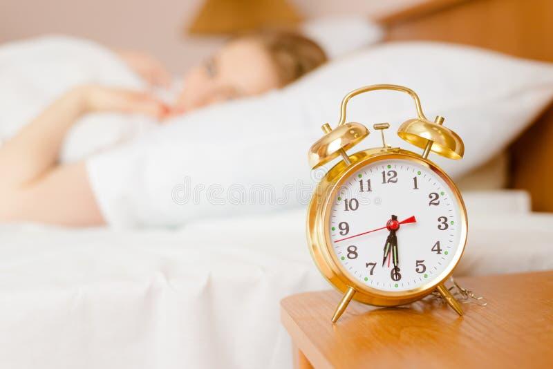 Rétro réveil avec la dame de sommeil sur le fond photos stock