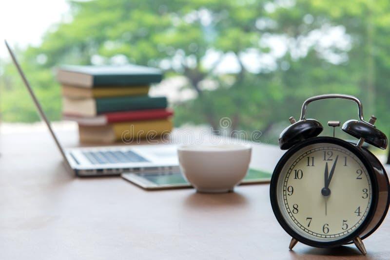 Rétro réveil avec la tasse de cappuccino sur la table dans le bureau, Cof photos libres de droits