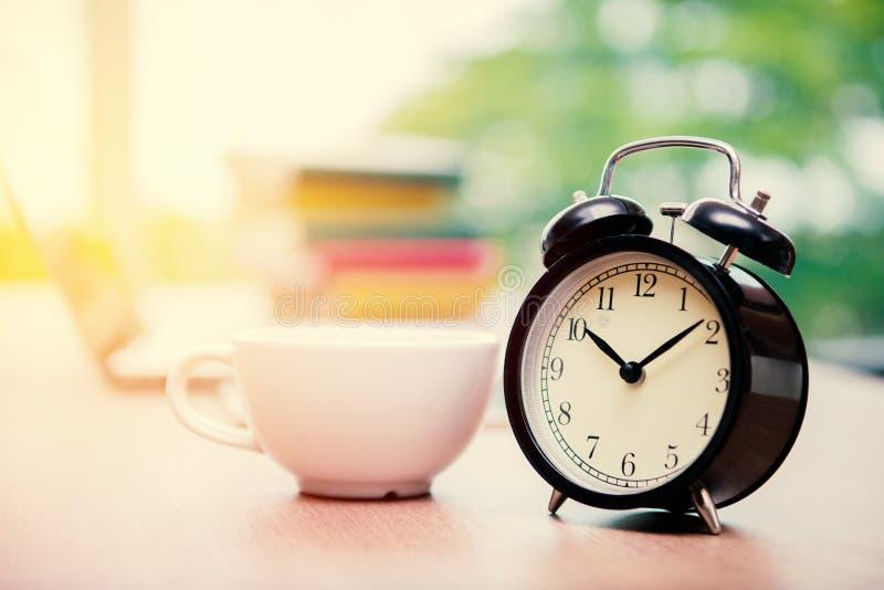 Rétro réveil avec la tasse de cappuccino sur la table dans le bureau, Cof image libre de droits