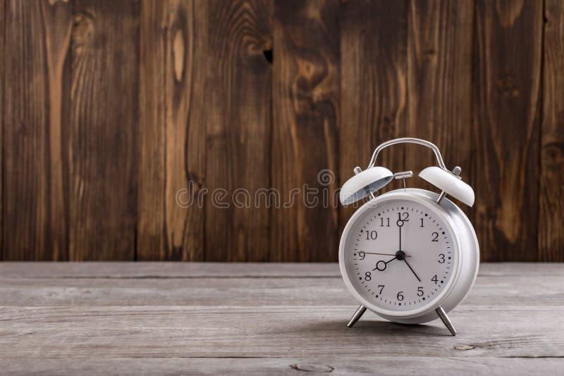 Rétro réveil blanc sur la table en bois photographie stock