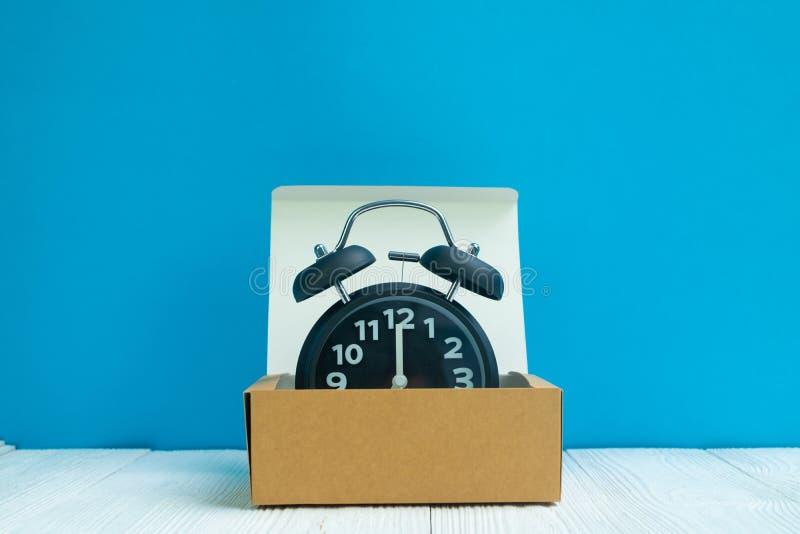 Rétro réveil dans la boîte ou le plateau en carton brune de la livraison sur le whi photo libre de droits