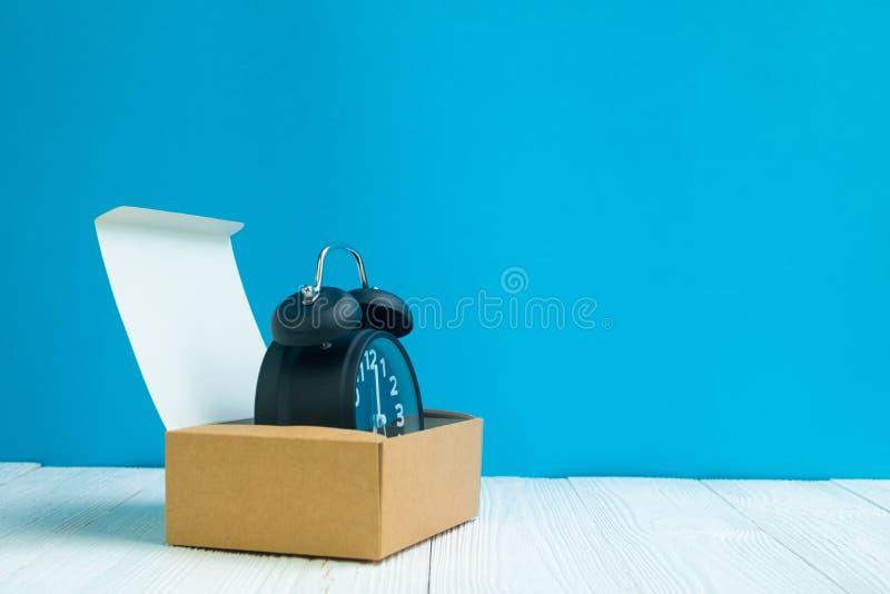 Rétro réveil dans la boîte ou le plateau en carton brune de la livraison sur le whi image stock