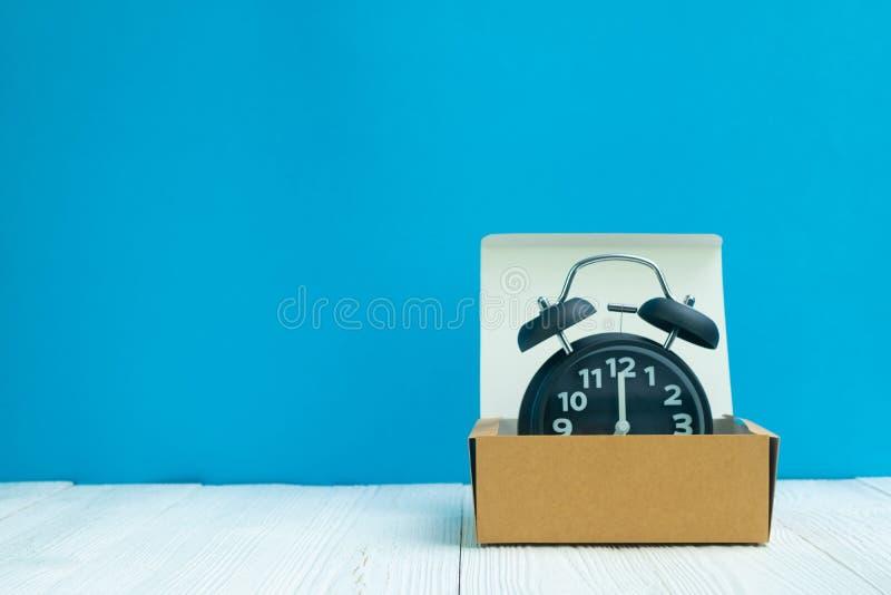 Rétro réveil dans la boîte ou le plateau en carton brune de la livraison sur le whi images stock