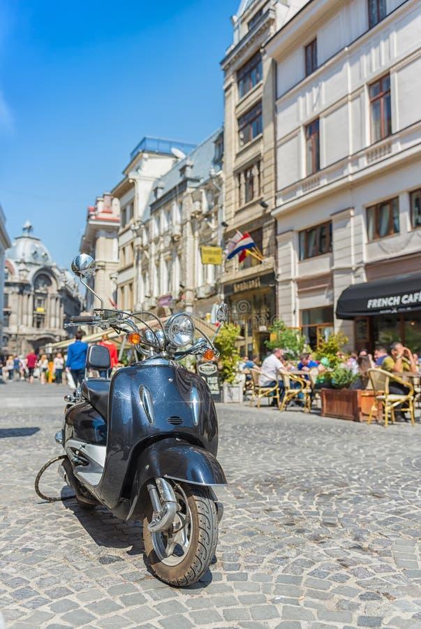 Rétro scooter bleu sur la vieille rue de ville de Bucarest photographie stock libre de droits