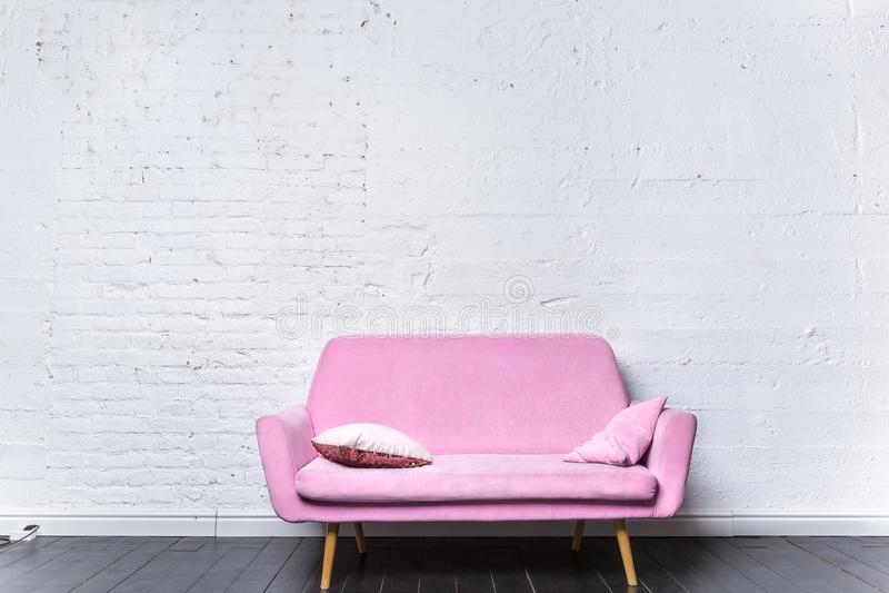 Rétro sofa rose contre le mur de briques blanc photos libres de droits