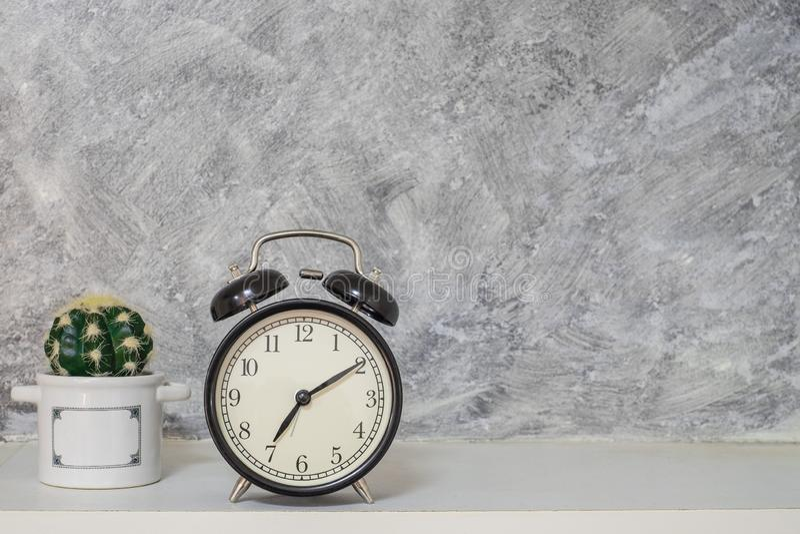 Rétro style de cru d'horloge de noir d'alarme avec le petit cactus Mur nu de grenier de ciment photo stock