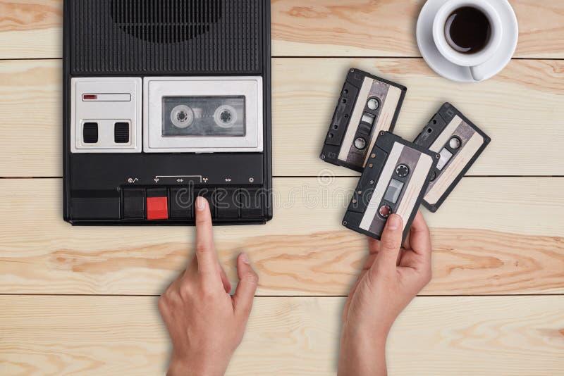 Rétro substance, vieux articles, souvenirs Mains alimentant le vieux magnétophone à cassettes de bande et tenant trois cassettes  photographie stock