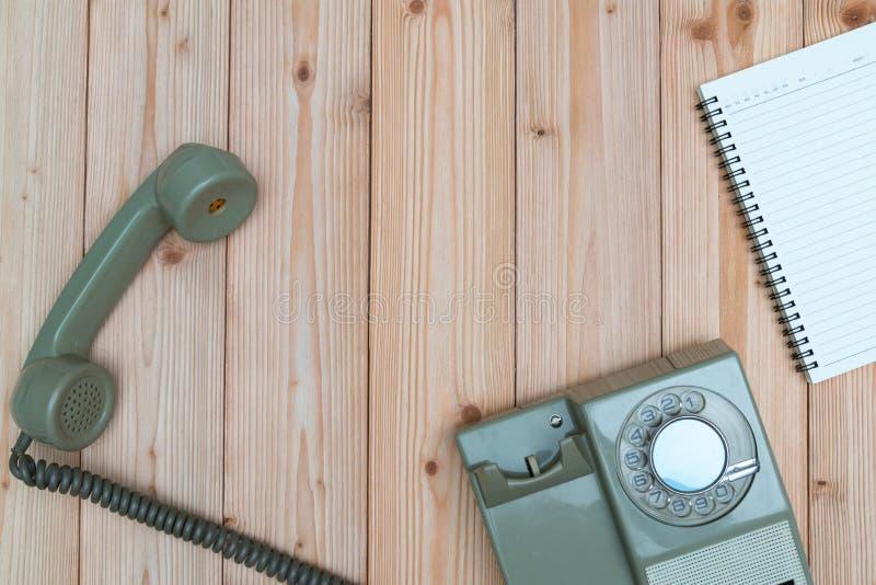 Rétro téléphone rotatoire avec le câble et le papier ou le noteb vide blanc photo stock