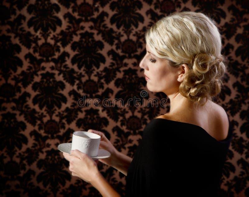Rétro thé ou café potable de regard de femme photographie stock libre de droits