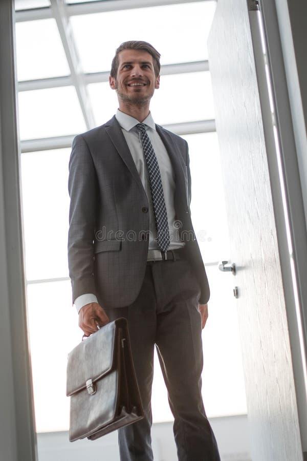 Rétro type homme d'affaires de sourire ouvrant la porte à son bureau image stock