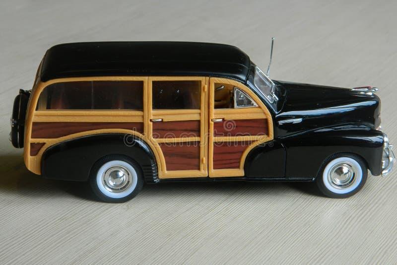 Rétro voiture noire de jouet sur la surface rayée grise Modèle de voiture de sport classique de cru avec les ombres et le foyer p photo stock