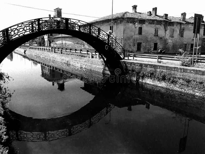 Rétro vue d'effet de cru d'un vieux pont au-dessus de Naviglio Pavese à Milan avec les maisons antiques sur le fond - noir et bla photographie stock