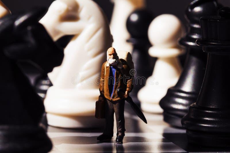Rétros chiffres de voyageur et d'échecs à bord Vieux voyageur dans l'échiquier photos stock