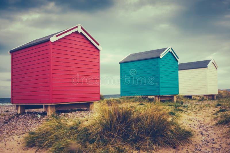 Rétros huttes britanniques de plage photo stock