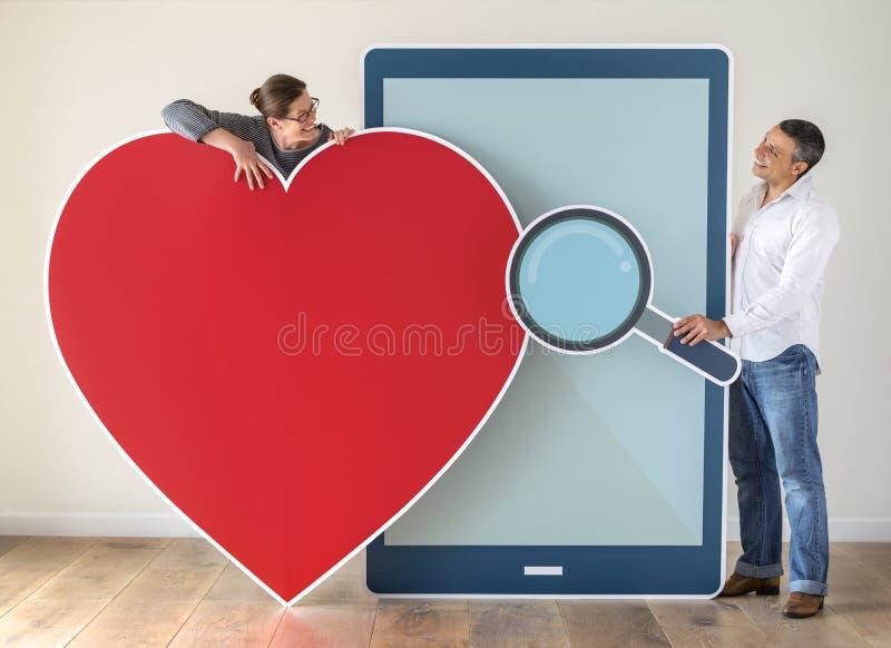 Réunion de couples par un APP datant image stock
