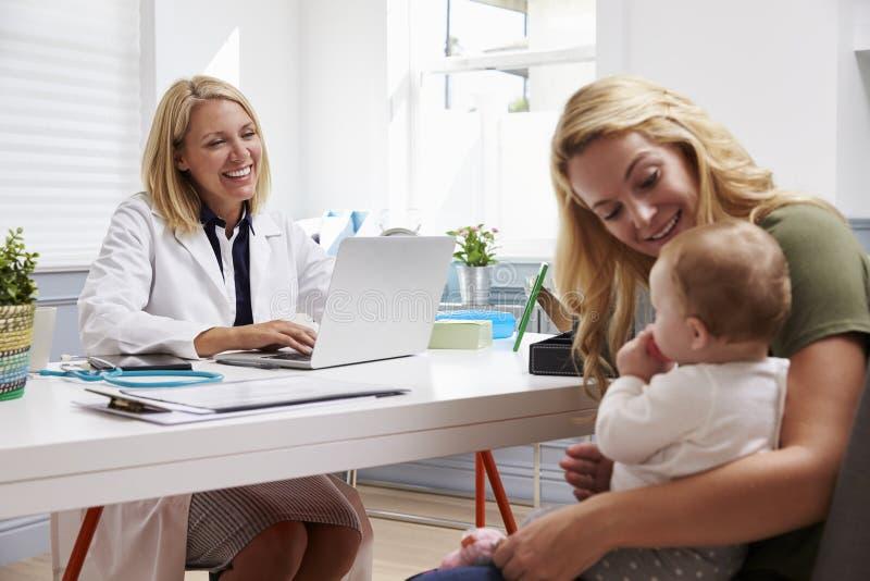 Réunion de mère et de bébé avec docteur féminin In Office photo libre de droits
