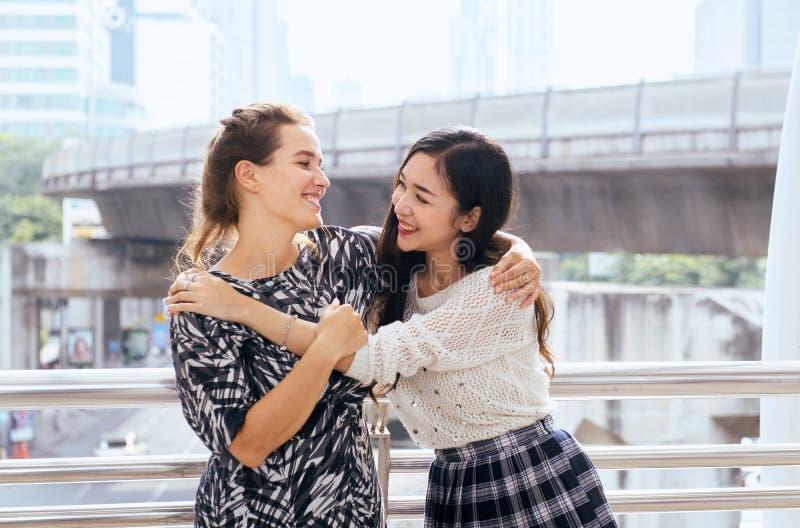 Réunion de main de femme, salutation heureuse de l'ami deux étreignant dans la ville photo libre de droits