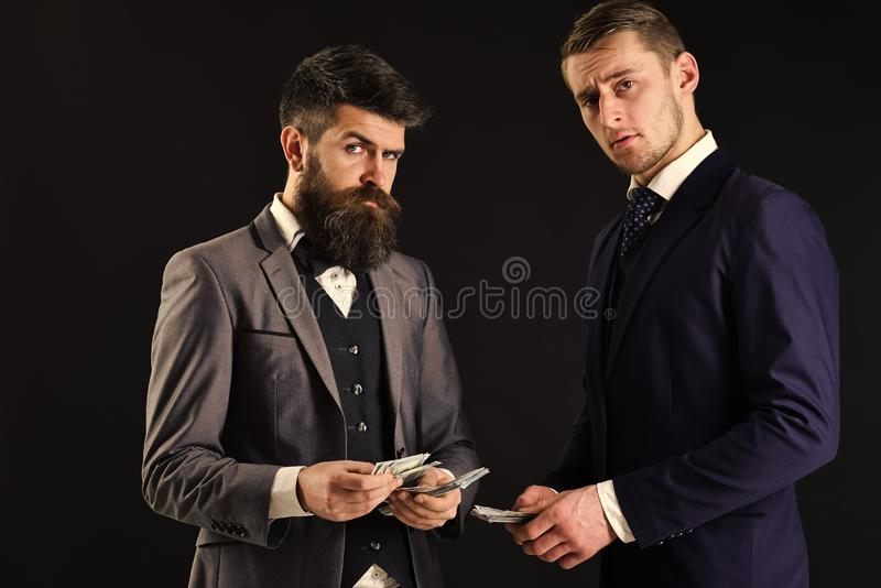 Réunion des hommes d'affaires honorables, fond noir Homme avec la barbe sur le visage sérieux comptant l'argent, salaire à l'asso images libres de droits