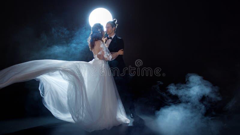 Réunion mystérieuse et romantique, les jeunes mariés sous la lune Étreintes ensemble Homme et femme, robe de mariage images libres de droits